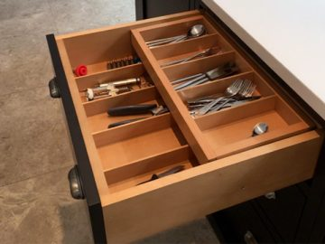 Cutlery drawer with sliding upper compartment